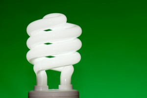 Compact fluorescent lightbulb (CFL) against a green background